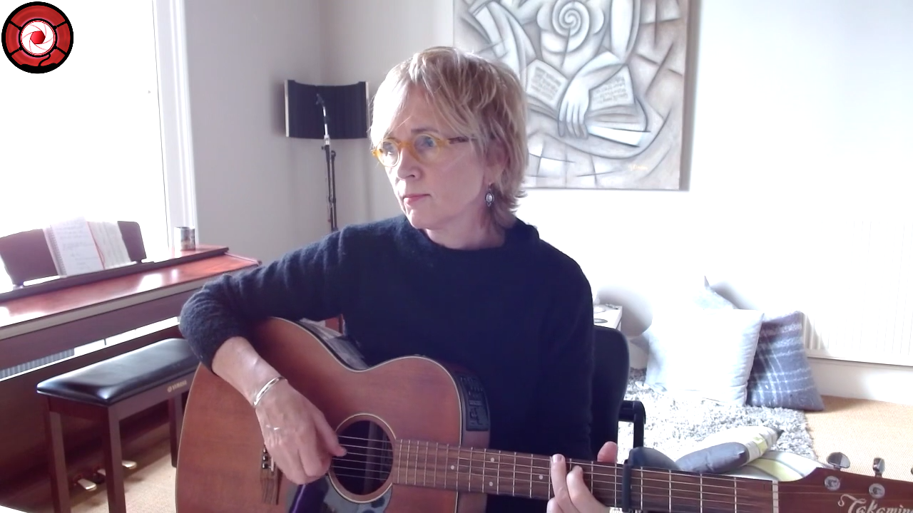 Kathy Muir sitting at her desk and playing guitar