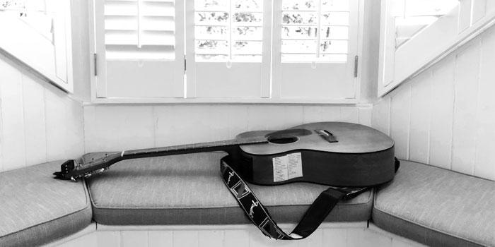 Takamine Guitar lying gently on a bay window